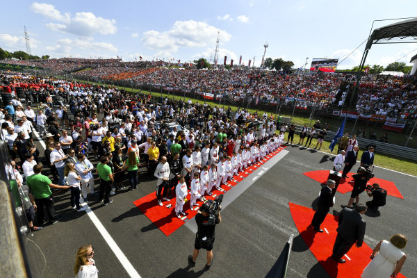 The drivers stand with the Grid Kid mascots for the national anthem prior to the start