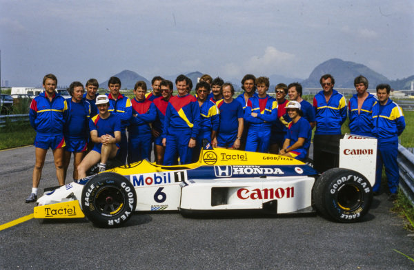 The Williams team with Nelson Piquet's Williams FW11 Honda. Piquet sits on the rear-right tyre, while Nigel Mansell sits on the front-right.