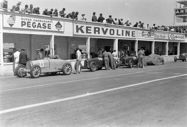 Robert Brunet's Bugatti T51 (#6), Guy Moll's Alfa Romeo Tipo B (#16), and Achille Varzi's Alfa Romeo Tipo B (#14), are worked on in the pits.
