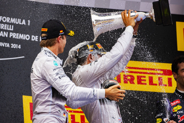 Lewis Hamilton, 1st position, and Nico Rosberg, 2nd position, celebrate on the podium.