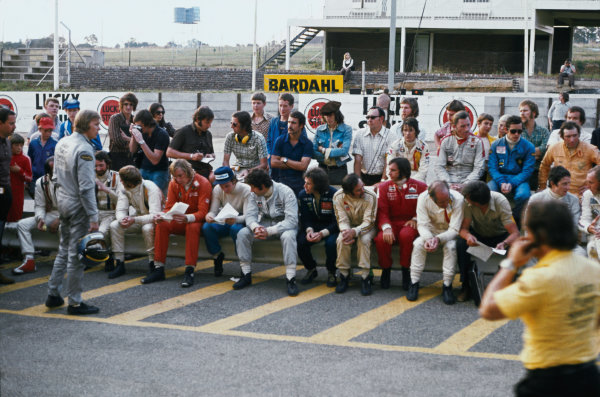 Kyalami, South Africa. 30 March 1974. Ronnie Peterson looks for somewhere to sit for the drivers meeting, portrait.  World Copyright: LAT Photographic. Ref:  74SA21