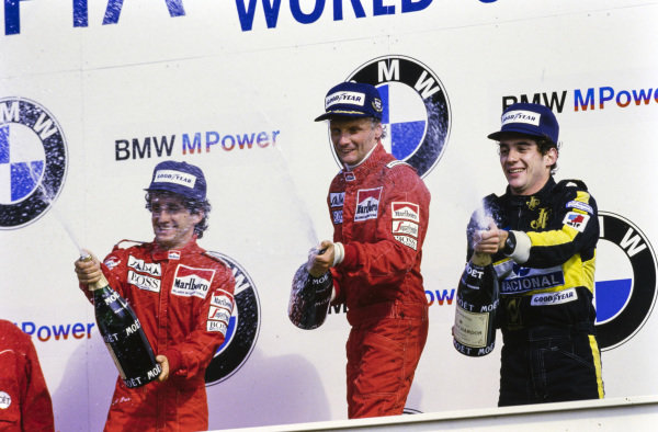 Niki Lauda, 1st position, celebrates his final grand prix win alongside Alain Prost, 2nd position, and Ayrton Senna, 3rd position, on the podium.