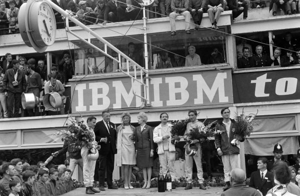 Bruce McLaren and Chris Amon, 1st position, stand at either end of the podium, with Henry Ford II and his wife, and P2.0 class winners Colin Davis and Jo Siffert, on the podium.