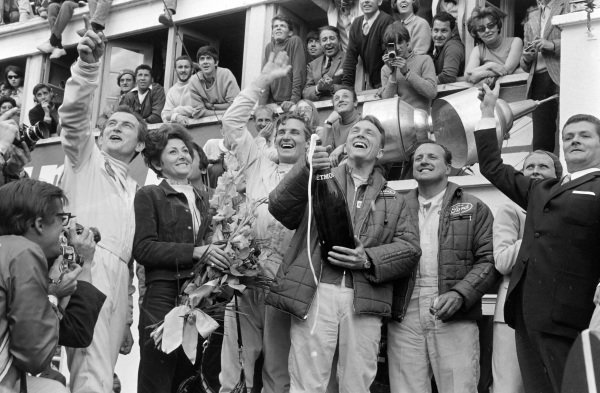 Dan Gurney / A.J. Foyt, Shelby-American, Ford GT40 Mk.IV, 1st position, celebrate victory, on the podium, with Gurney popping and spraying his Champagne which would establish a tradition in motor racing that stands to this day.