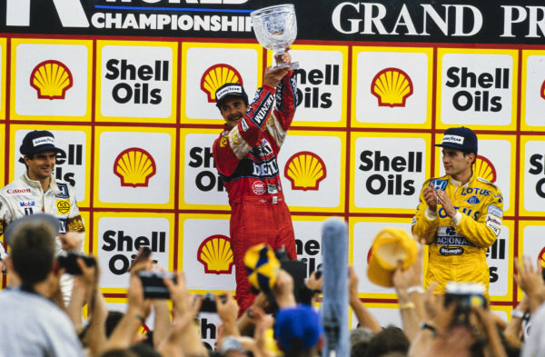 Nigel Mansell, 1st position, raises his trophy on the podium. Nelson Piquet, 2nd position, and Ayrton Senna, 3rd position, are alongside.
