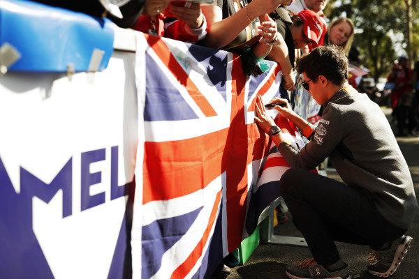 Lando Norris, McLaren, signs a Union Jack UK flag.