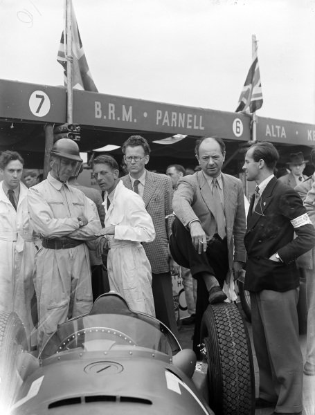 Peter Walker stand behind his BRM P15 while team boss, Raymond Mays puts his foot on a wheel.