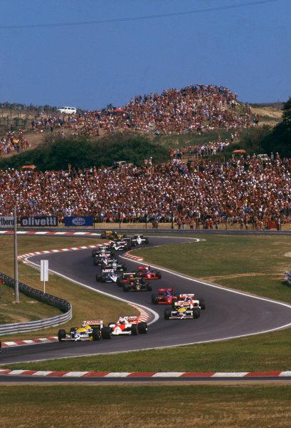 Hungaroring, Budapest, Hungary. 8-10 August 1986. Nelson Piquet (Williams FW11 Honda) leads Alain Prost (McLaren MP4/2C TAG Porsche), Nigel Mansell (Williams FW11 Honda) and Keke Rosberg (McLaren MP4/2C TAG Porsche) at the start. Action. Ref: 86 HUN 06. World Copyright - LAT Photographic
