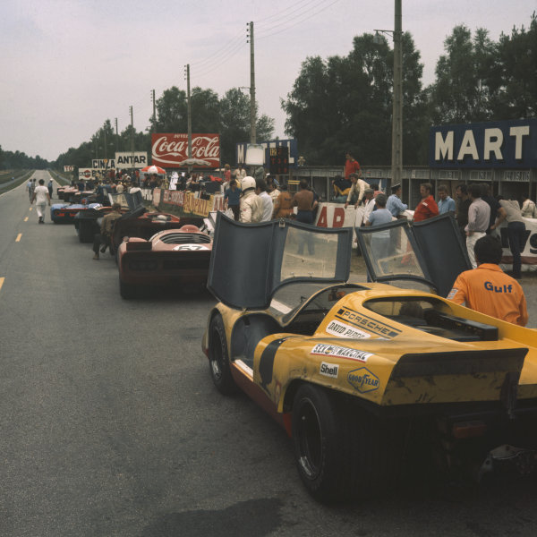 A line of cars are parked at Mulsanne Corner during the making of the Steve McQueen film Le Mans. A Porsche 917 of David Piper is in the foreground, behind a Chevron, Lola T170, Porsche 917 and a Matra MS12