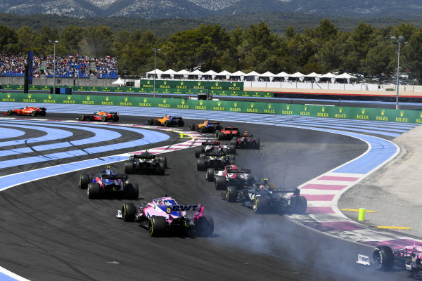 Charles Leclerc, Ferrari SF90, leads Max Verstappen, Red Bull Racing RB15, Carlos Sainz Jr., McLaren MCL34, Lando Norris, McLaren MCL34, Sebastian Vettel, Ferrari SF90, Pierre Gasly, Red Bull Racing RB15, Antonio Giovinazzi, Alfa Romeo Racing C38, Daniel Ricciardo, Renault R.S.19, and Nico Hulkenberg, Renault R.S. 19, and the remainder of the field on the opening lap