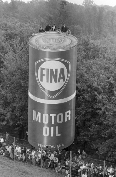 Fans atop an advertising board get a decent view of the race.