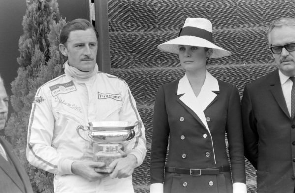 Graham Hill, 1st position, on the podium with Princess Grace and Prince Rainier III of Monaco.