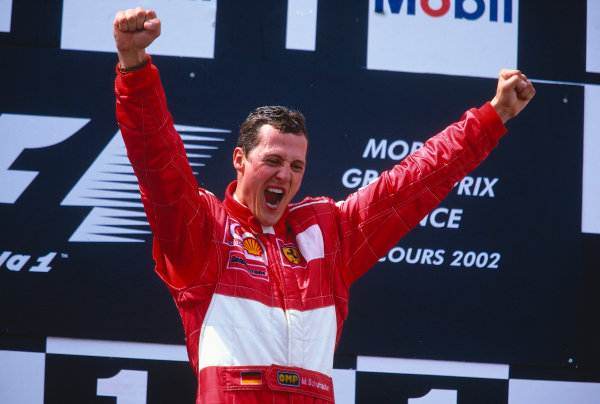 2002 French Grand Prix. Magny-Cours, France. 19-21 April 2002. Michael Schumacher (Ferrari) celebrates his 1st position and record equalling 5th formula one drivers World Championship on the podium. Ref-02 FRA 41. World Copyright - LAT Photographic
