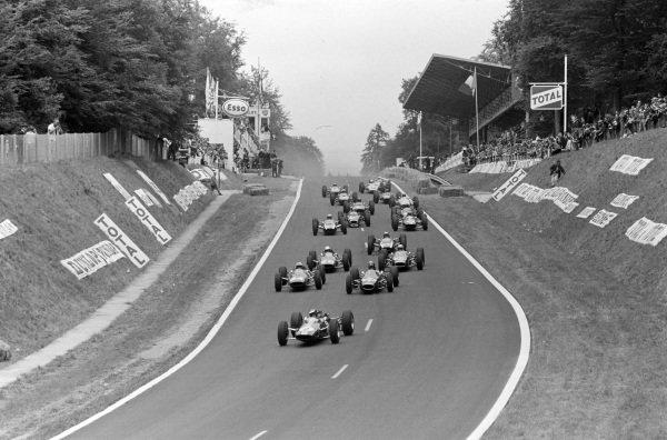 Jim Clark, Lotus 25 Climax, leads Dan Gurney, Brabham BT7 Climax, and John Surtees, Ferrari 158, as the field follow behind.