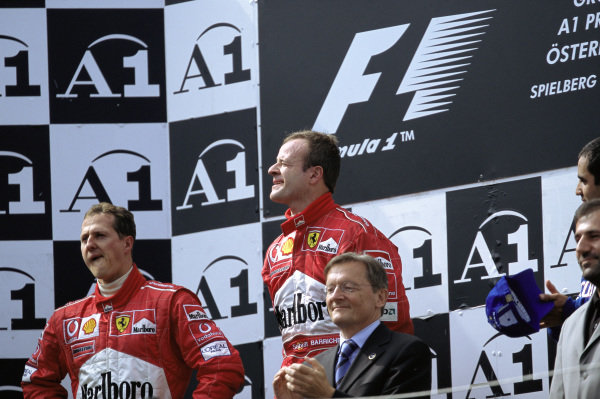 Rubens Barrichello, stands on top step of the rostrum reserved for the winner after controversially moving over for Michael Schumacher, standing in 2nd position, on the podium.