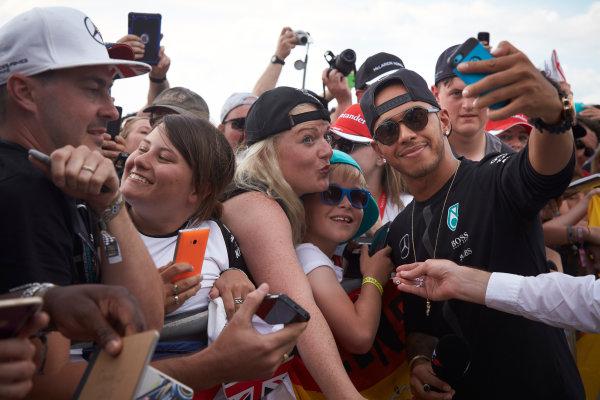 Silverstone Circuit, Northamptonshire, England. Saturday 4 July 2015. Lewis Hamilton, Mercedes AMG, with some fans. World Copyright: Steve Etherington/LAT Photographic ref: Digital Image SNE19043