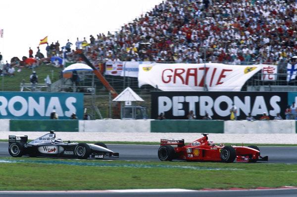 Sepang, Kuala Lumpur, Malaysia. 15-17 October 1999. Michael Schumacher (Ferrari F399) holds up Mika Hakkinen (McLaren MP4/14 Mercedes) alowing teammate Eddie Irvine to build a lead. Ref: 99MAL10. World Copyright - LAT Photographic