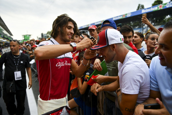Antonio Giovinazzi, Alfa Romeo Racing signs his hat that he has just given to a fan