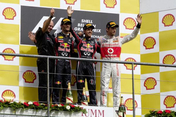 Adrian Newey, Mark Webber, 2nd position, Sebastian Vettel, 1st position, and Jenson Button, 3rd position, on the podium.