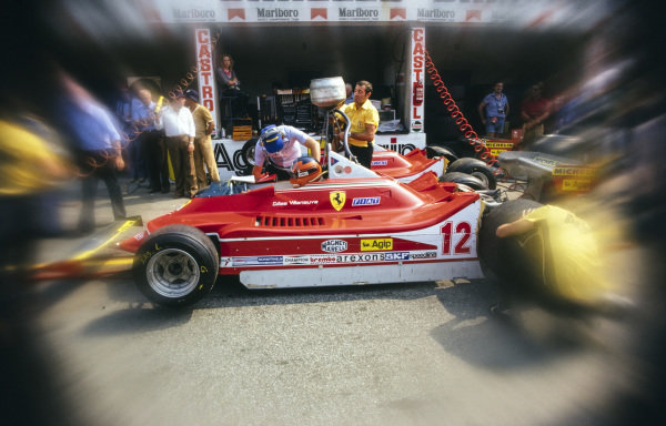 Gilles Villeneuve sits in his Ferrari 312T4B in the pit lane as it is refuelled.