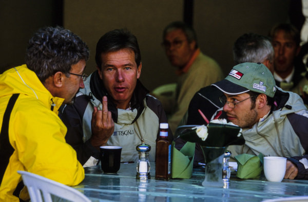 Craig Pollock flips the bird while in conversation with Eddie Jordan and Jacques Villeneuve.