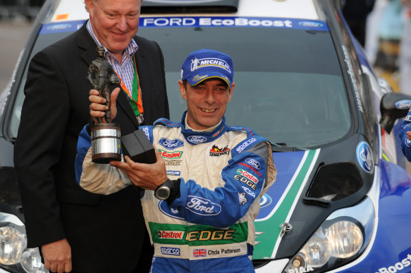 Chris Patterson (GBR) receives the Nigel Harris trophy for the top British co-driver, on the podium. FIA World Rally Championship, Rd10, Wales Rally GB, Day Three, Cardiff, Wales, 16 September 2012.