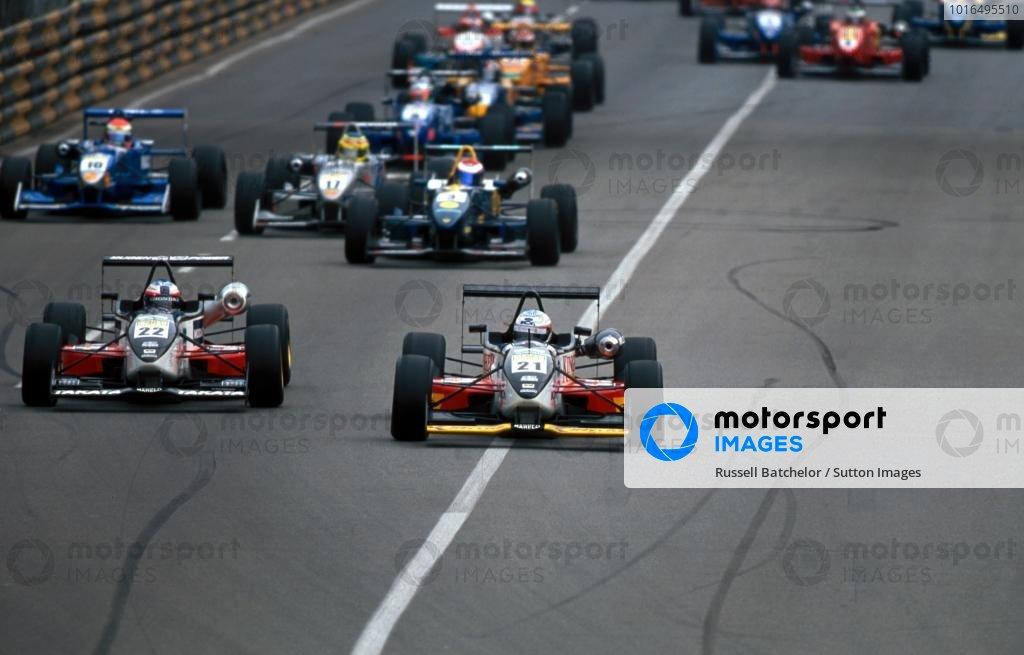 Takuma Sato (JPN) Carlin Motorsport Dallara Mugen Honda F300 (left) is lead by team mate and pole sitter Narain Karthikeyan (IND) at the start, but both were to crash out on the first leg. International Formula Three, Macau Grand Prix, Hong Kong, 16-19 November 2000.