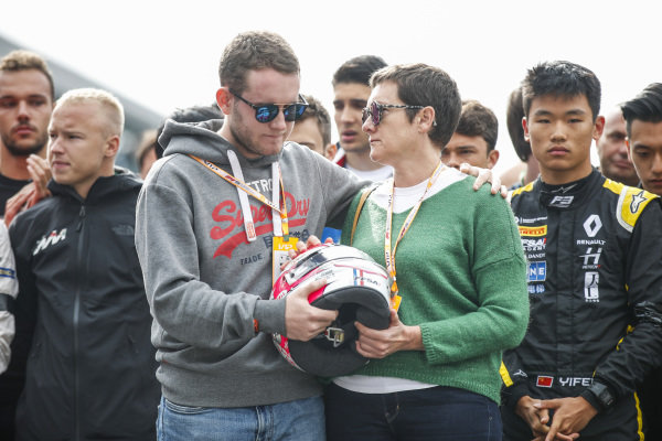 The Mother and Brother of Anthoine Hubert (FRA, BWT ARDEN) hold his helmet at the memorial.