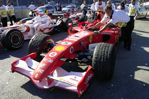 Michael Schumacher's Ferrari 248 F1 being pushed to scrutineering after the race.