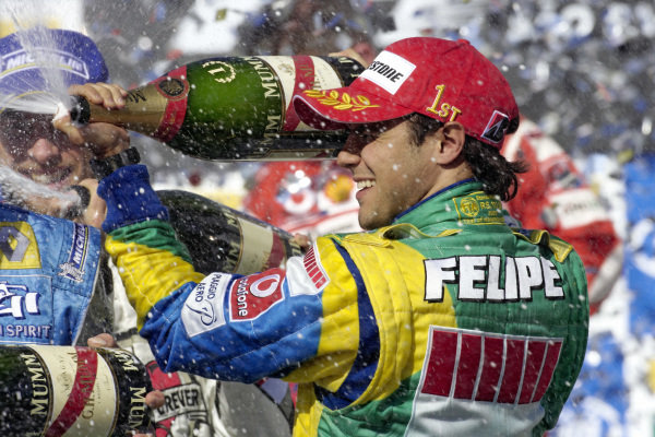Winner Felipe Massa spraying champagne in celebration on the podium.