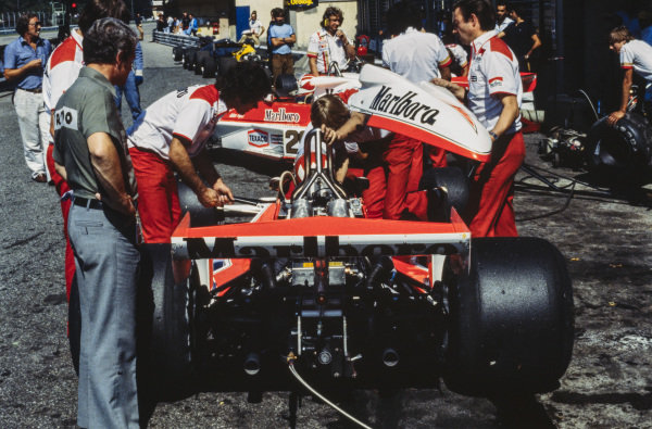 McLaren mechanics hold the engine cover of the Bruno Giacomelli McLaren M26 Ford. On the far right is future grand prix driver and Le Mans winner Johnny Dumfries, acting as a gofer for BS Fabrications.