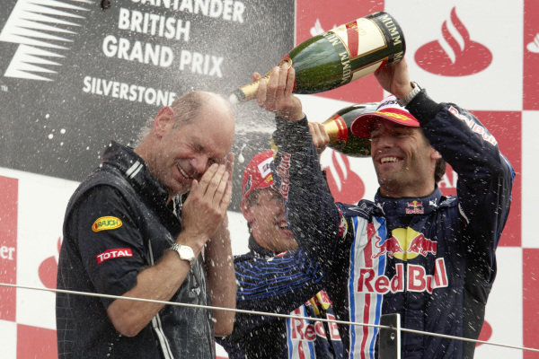 Adrian Newey gets a face full of champagne from winner Sebastian Vettel and 2nd position Mark Webber.