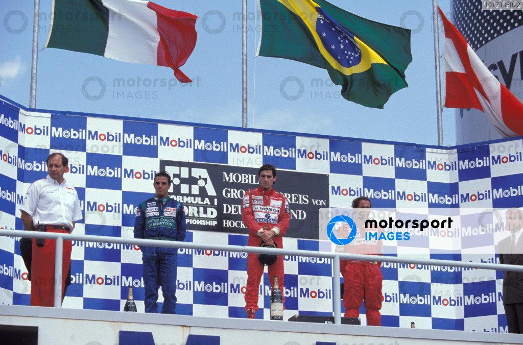 Ron Dennis, Alessandro Nannini, Ayrton Senna, and Gerhard Berger on the podium.