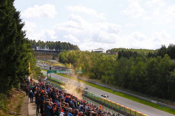Charles Leclerc, Alfa Romeo Sauber C37, passes an orange flare and spectators.