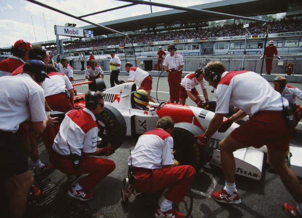 Ayrton Senna sits aboard his McLaren MP4-8 Ford, as the team performs pit stop practice.