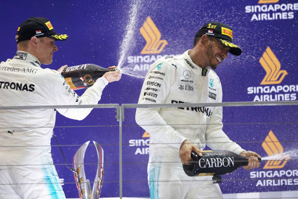 Marina Bay Circuit, Marina Bay, Singapore. Sunday 17 September 2017. Valtteri Bottas, Mercedes AMG, 3rd Position, sprays Lewis Hamilton, Mercedes AMG, 1st Position, with Champagne on the podium. World Copyright: Steve Etherington/LAT Images  ref: Digital Image SNE17319