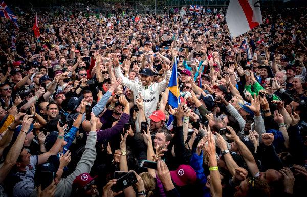 Silverstone, Northamptonshire, UK.  Sunday 16 July 2017. Lewis Hamilton, Mercedes AMG, 1st Position, celebrates victory with some crowd surfing. World Copyright: Dunbar/LAT Images  ref: Digital Image _X4I8865