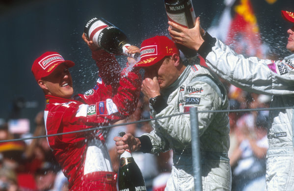 2001 United States Grand Prix.Indianapolis, Indiana, USA.28-30 September 2001.Michael Schumacher (Ferrari) 2nd position and David Coulthard (McLaren Mercedes) 3rd position give Mika Hakkkinen (McLaren Mercedes) 1st position a champagne shower on the podium.Ref-01 USA 22.World Copyright - LAT Photographic