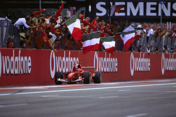 The team wave Italian flags as Michael Schumacher, Ferrari F2004 crosses the finish line in 2nd position.