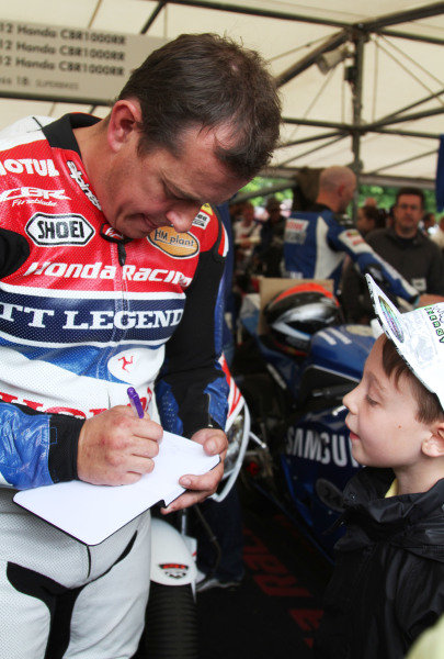 Goodwood Estate, West Sussex, England. 28th June - 1st July 2012. Isle of Man TT legend John McGuinness signs an autograph for a young fan. World Copyright: Kevin Wood/LAT Photographic Ref: IMG_9343a