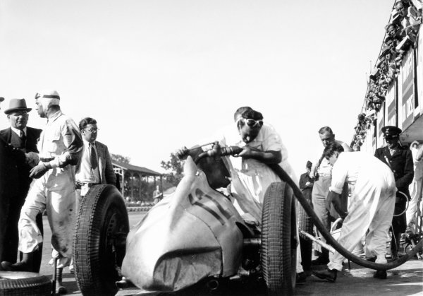 Monza, Italy. 11 September 1938.Rudolf Caracciola talks to Max Sailer (out of car, left) as Manfred von Brauchitsch takes over the Mercedes-Benz W154, 3rd position, pitstop, action, refuelling.World Copyright: Robert Fellowes/LAT PhotographicRef: 38ITA02