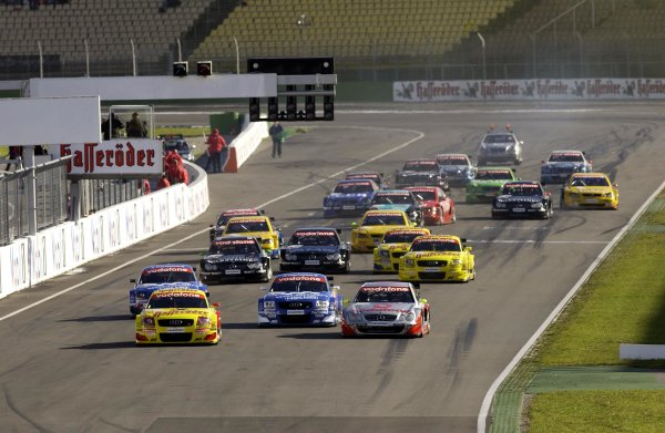 2002 DTM Championship.Hockenheim, Germany. 5-6 October 2002.Laurent Aiello (Abt Audi TT-R) and Bernd Schneider (HWA/Mercedes CLK DTM) lead the field down to the Nordkurve at the start.World Copyright - Andre Irlmeier/LAT Photographic