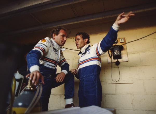 Jacky Ickx and Jochen Mass, Rothmans Porsche team-mates, talk in the pits.