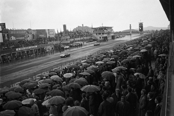 View from the grandstand opposite the pits as spectators shelter under umbrellas.