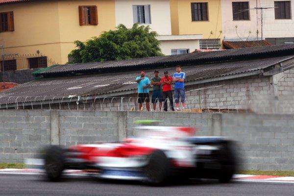 Timo Glock (GER) Toyota TF108 passes fans in the favelas. Formula One World Championship, Rd 18, Brazilian Grand Prix, Practice Day, Interlagos, Sao Paulo, Brazil, Friday 31 October 2008.