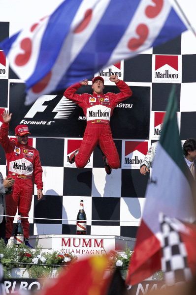 Michael Schumacher, 1st position, celebrates with a jump on the podium. Rubens Barrichello, 2nd position, is alongside.