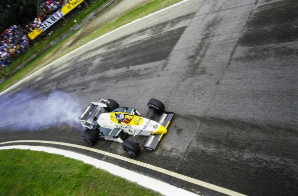 Keke Rosberg, Williams FW09B Honda, trails smoke.