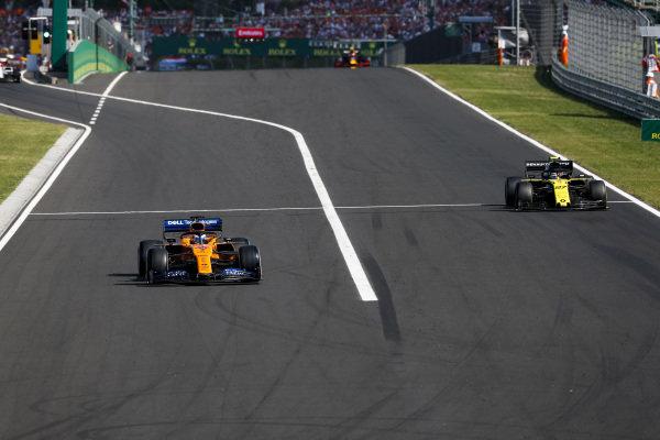 Carlos Sainz Jr., McLaren MCL34, leads Nico Hulkenberg, Renault R.S. 19