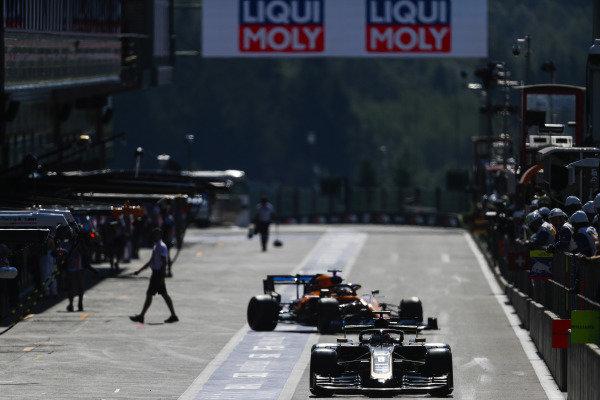 Romain Grosjean, Haas VF-19, leads Carlos Sainz Jr., McLaren MCL34, out of the pits