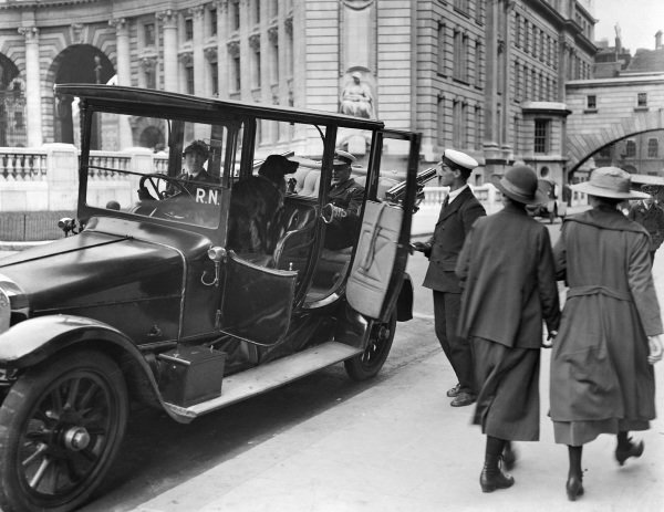 A member of the Women's Royal Naval Service prepares to driver an officer and his dog in an official Navy car.